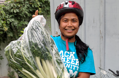 Mildred, staff at BCCF, holding some veggies in a bag and smiling. She is wearing a teal BCCF t-shit!