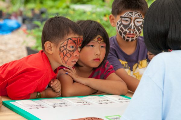 Kids with painted faces take part in an activity at the annual Black Creek Community Farm Festival.