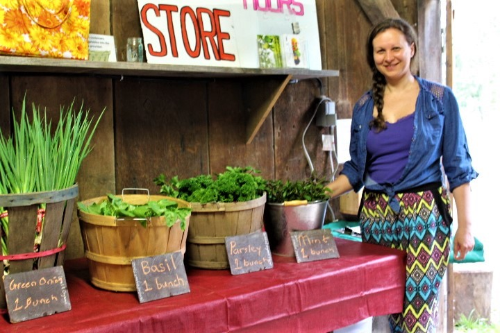 woman standing in front of a table with many vegetables on it for sale at the farm market